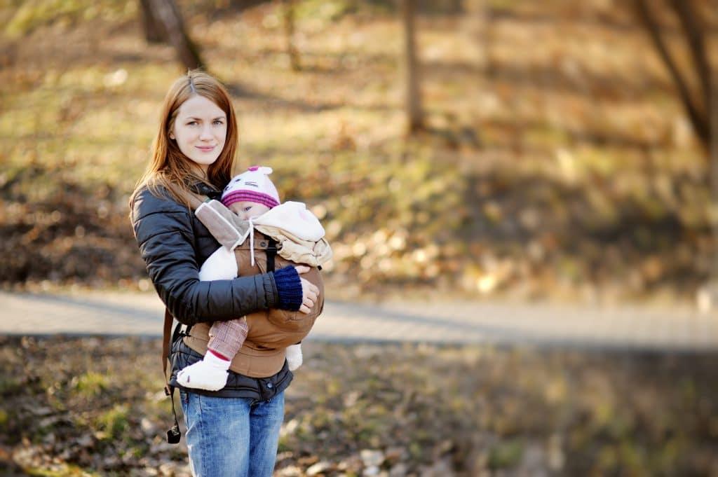 Mor med baby i bæresele, der kan forværre delte mavemuskler.