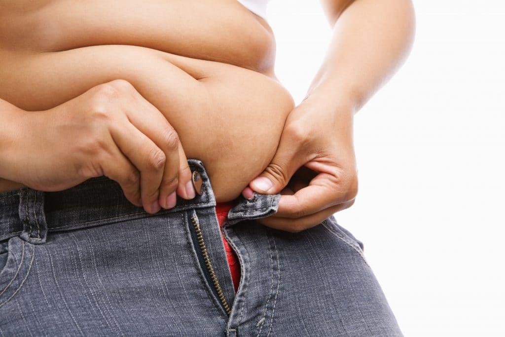 Tyk kvinde der ikke har flad mave prøver at lukke sine jeans