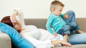 Træt mor på en sofa spørger om lidt træning er bedre end ingen træning