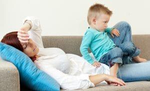 Træt og dvask mor på sofa med lille søn på skødet