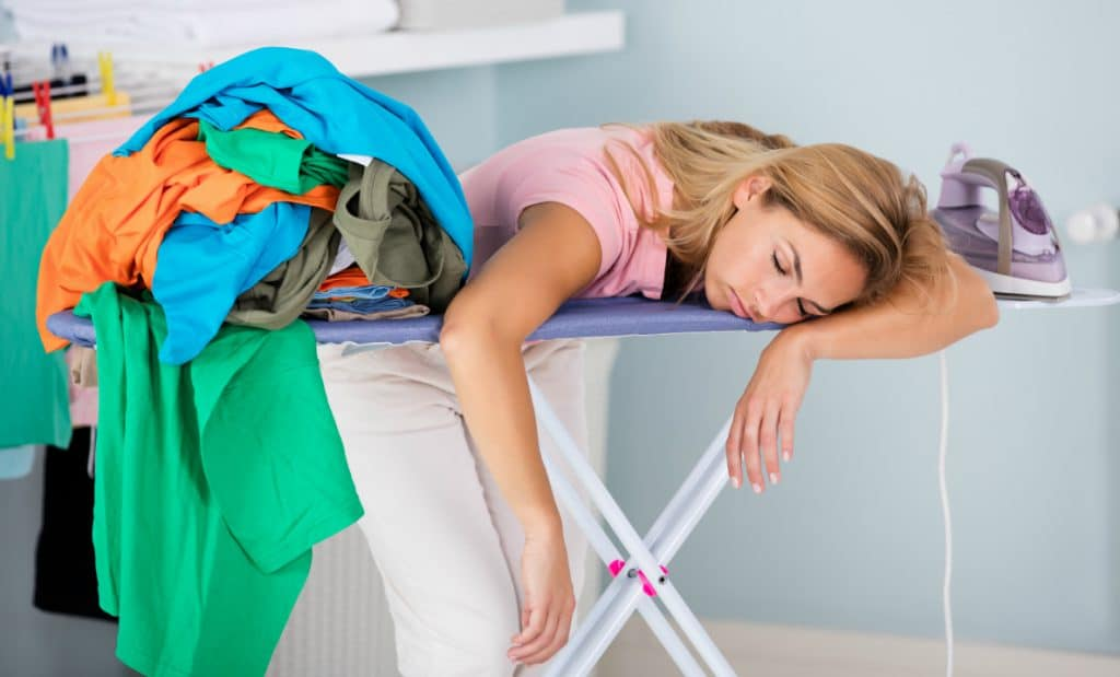 Træt mor sover over strygebræt