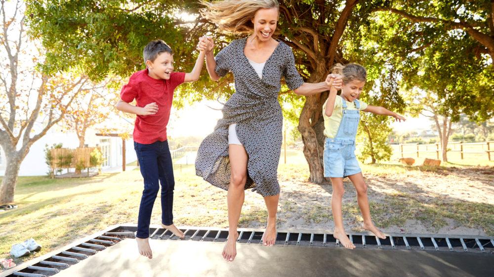Mor med to børn hopper i trampolin